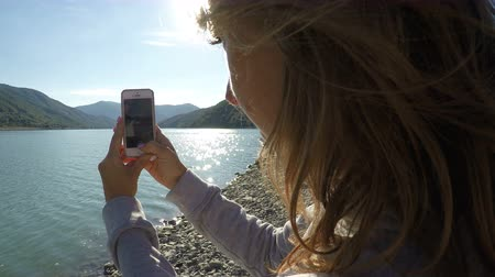 wavelet : Female filming mountain landscape and river on cell phone on a sunny day