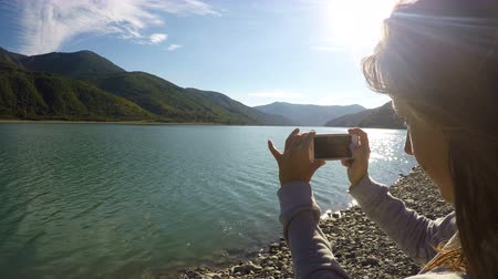 wavelet : Young lady recording video of sunlit mountain scenery and river using smartphone