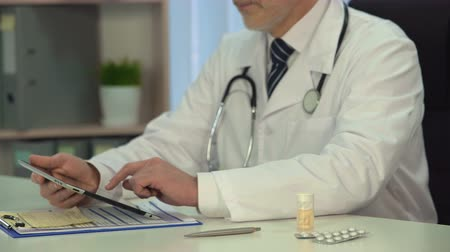 pólos : Male doctor consulting patient online, checking diagnosis on tablet in clinic