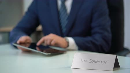 evasion : Tax collector using tablet pc with database of debtors with bad credit history Stock Footage