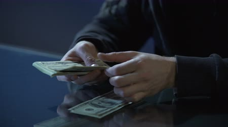 evasion : Hands of contract killer or bank robber counting money paid for committing crime Stock Footage