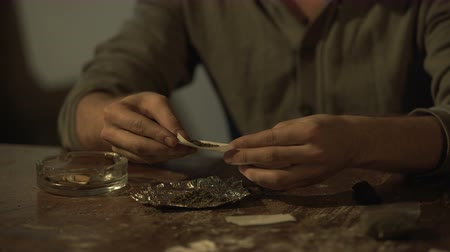 прокатка : Young man making cannabis cigarette to ease stress, abuse of psychoactive drug