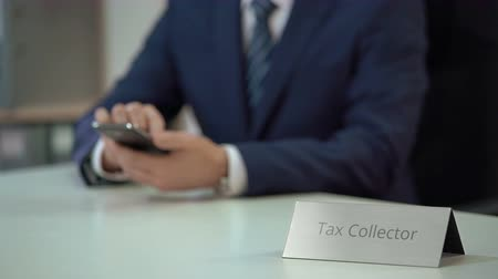evasion : Busy male tax collector typing and sending messages to debtors from smartphone Stock Footage