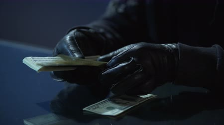 evasion : Criminal in black gloves counting bundle of money earned for committing crime Stock Footage