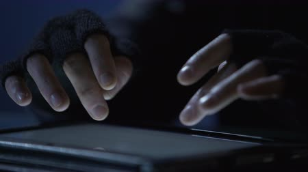 езда с недозволенной скоростью : Closeup of criminals hands scrolling pages on tablet touchscreen, cybercrime