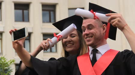 aluno : Female and male graduates in academic dresses and caps shooting video on phone