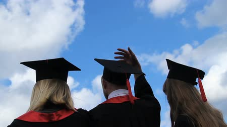 promoce : Happy future of graduates, three students throwing academic caps up in the air