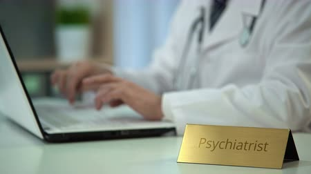 male : Psychiatrist typing report on laptop computer, doctor consulting patients online
