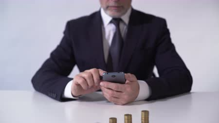 lucrative : Serious man using smartphone app, calculating income from business contract
