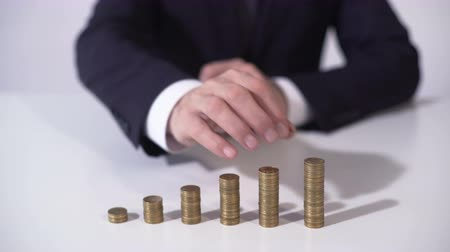 lucrative : Banker putting coin on pile, deposit interest growing, successful investment Stock Footage