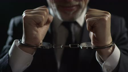 kajdanki : Angry criminal imprisoned in handcuffs, unfair businessman punished for offense