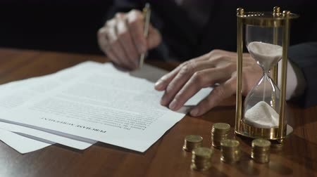 lucrative : Male buyer or seller signing purchase agreement, money and hourglass on table Stock Footage