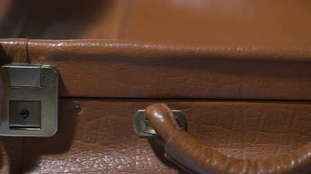 dava : Man shutting vintage leather suitcase, packing for vacation, preparing for trip