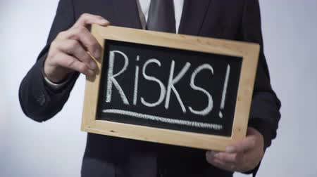 решить : Risks with exclamation mark written on blackboard, business person holding sign Стоковые видеозаписи