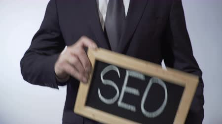 on site research : SEO written on blackboard, businessman holding sign, business concept, strategy Stock Footage