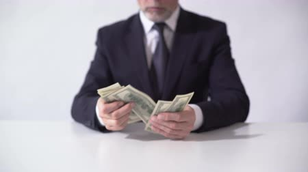 lucrative : Rich man counting bundle of dollar banknotes, businessman estimating income Stock Footage