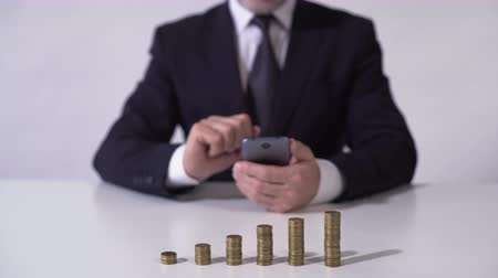 lucrative : Man using mobile app, calculating income from deposit or successful investment
