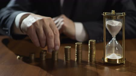lucrative : Businessman putting coins on piles, sand flowing in hourglass, deposit interest Stock Footage