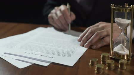 lucrative : Serious businessman signing purchase agreement as time flows with sand in clock Stock Footage