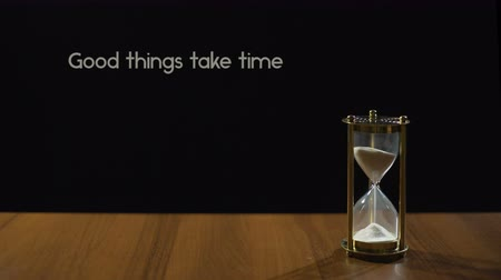 levou : Good things take time, popular expression about patience, sandglass on table