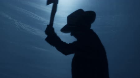 mortal : Malicious dwarf silhouette in hat cutting something with sharp axe, nightmare