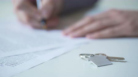 купить : Person signing real estate purchase agreement, key from apartment on table
