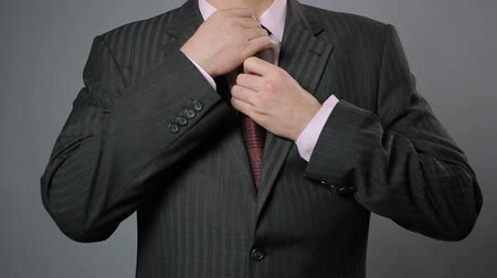 red tie : Businessman adjusting his necktie and jacket, close-up. Stylish mens wear