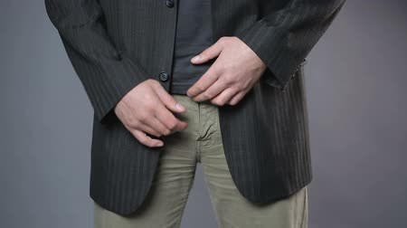 definição : Male in black jacket pulling his pants zipper, embarrassment, mans health