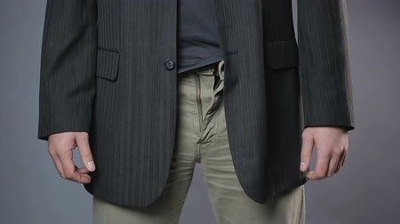 definição : Slim man zipping and unzipping pants zipper, mans clothes, close-up shot