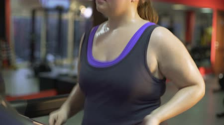 nadváha : Strong overweight woman working hard to lose weight, sweating on treadmill