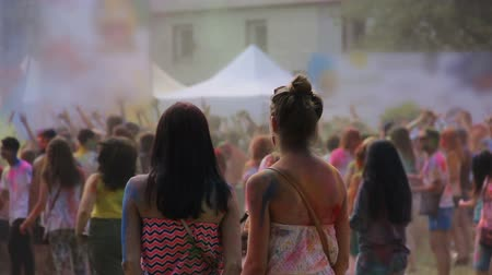 multikulturális : Female friends covered in colorful powder enjoying cool Holi festival at park Stock mozgókép
