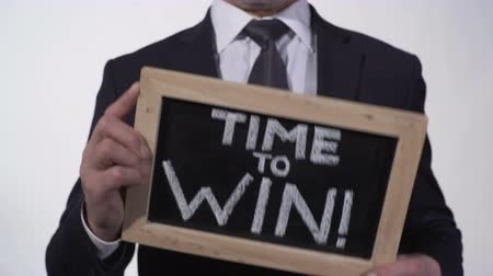 написанный : Time to win motivation phrase on blackboard in businessman hands, inspiration