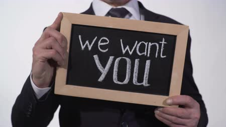 av : We want you phrase on blackboard in businessman hands, promising job offer Stok Video