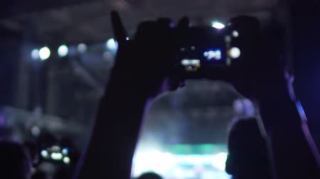 bálvány : Happy fan shooting video at music concert, enjoying favorite band performance Stock mozgókép