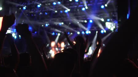 spotlights : Silhouettes of fans waving hands in brightly illuminated concert hall, dancing