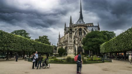 naživu : Notre-Dame de Paris garden with fountain, visitors viewing landmark, timelapse