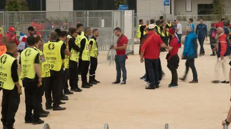steward : Stadium stewards standing in front of gate before game, spectators moving around
