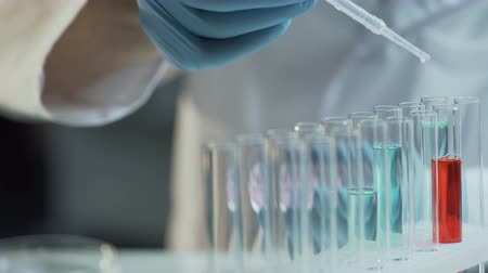 consistency : Lab worker adding concentrate to different reagents to follow reactions dynamics Stock Footage