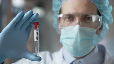 aids : Laboratory expert holding blood test for HIV antibodies, infection prevention