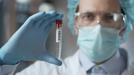 fatality : Special laboratory employee showing experimental Ebola virus vaccine, healthcare