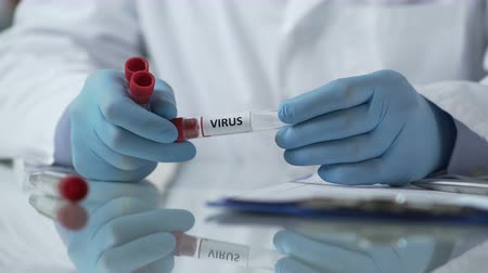 помощник : Lab assistant describing test tubes with viruses and adding them to database