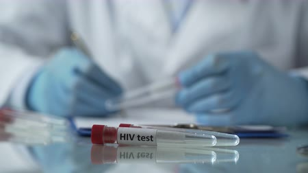dispensary : Lab worker filling in test results forms, holding plastic tube with HIV sample