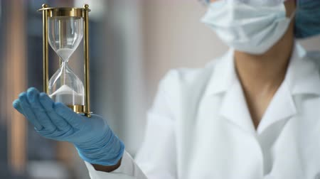 grit : Medical worker holding sand hourglass on palm, terminal disease, life expiring Stock Footage