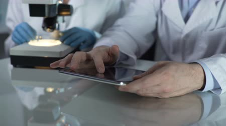 investigating : Male scientist scrolling tablet screen, colleague working with microscope nearby