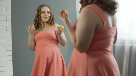 nadváha : Happy and satisfied with oversize body girl eating donuts in front of mirror Dostupné videozáznamy