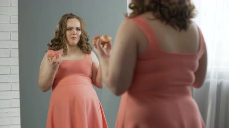 artı : Depressed overweight lady chewing donuts in front of mirror, eating disorder Stok Video