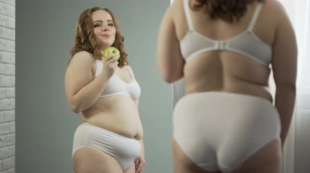 artı : Plus-size lady eating apple in front of mirror, enjoying results of healthy diet