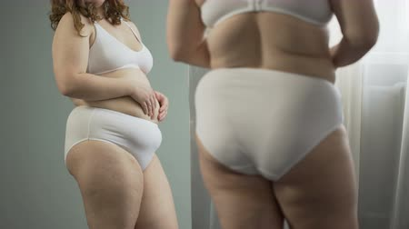 associated : Young woman looking at fat belly, wants to lose excess weight, risk of diseases
