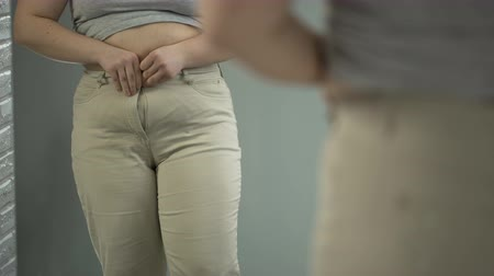 потеря : Girl getting into new pants after long grueling weight loss diet, achieving goal Стоковые видеозаписи
