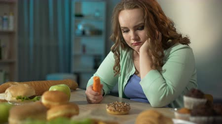 high calories : Overweight girl looking at donut and holding carrot in her hand, healthy diet Stock Footage